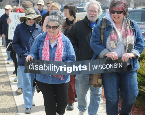 group of people for disability rights marching with sign that says DRW